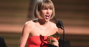 Taylor Swift accepting the award for the Album of the Year onstage during the 58th Annual Grammy music awards in Los Angeles. Photograph: Robyn Beck/AFP/Getty Images
