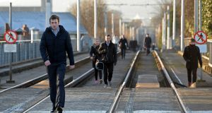 Luas Strike Commuters take to the tracks and walk along the Luas line at Ranelagh. Photograph: Eric Luke / The Irish Times
