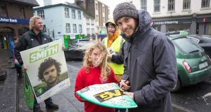 Green Party candidate Fergal Smith signs a piece of one of his broken surfboards for Finn Curran (7) while canvassing in Ennis, Co Clare. Photograph: Eamon Ward