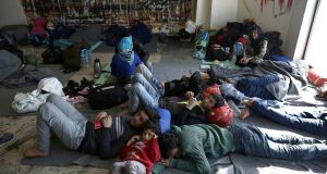 Migrants and refugees rest inside the old airport building in Athens, which is used as a temporary hosting shelter, on Friday. Photograph: Simela Pantzartzi/EPA.