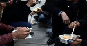 Afghan migrants receive food from volunteers in a square outside Victoria metro station in central Athens.  Photograph: Simela Pantzartzi/EPA