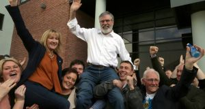 Sinn Féin leader Gerry Adams is held aloft after being re-elected. Photograph: AFP/Getty Images