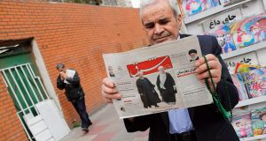 A man holds a copy of the daily 'Shargh' newspaper with pictures of Iran's president Hassan Rouhani and former president Akbar Hashemi Rafsanjani under the headline  'Decisive victory for the reformist, outside a kiosk in Tehran on Sunday. Photograph: Abedin Taherkenareh/EPA