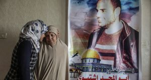 The mother and a sister of Mahmoud Ishtiwi, a former commander in the armed wing of Hamas, stand by a poster bearing his image at their home in Gaza. The one time leader of Hamas fighters from a storied family of Hamas loyalists was accused of homosexuality and executed by his former comrades. Photograph: Wissam Nassar/New York Times