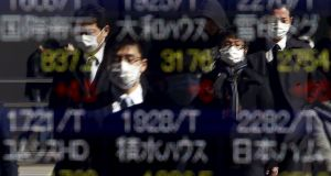 Pedestrians wearing masks are reflected in an electronic board showing various stock prices outside a brokerage in Tokyo, Japan. Photograph: Yuya Shino/Reuters