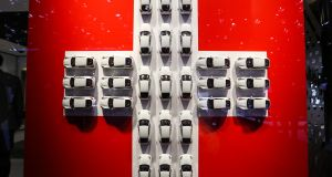 Model white cars sits in a cross formation of the Swiss national flag