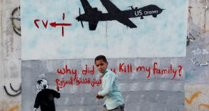 A boy passes a mural in Yemen: Fulfilling a commitment made by President Barack Obama in 2013, the US government plans to release details of the number of militant suspects and civilians killed in drone strikes since 2009. Photograph: Mohammed Huwais/AFP/Getty