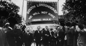 Unionist leaders HT Barrie, Edward Carson and Frederick Smith are cheered on by supporters at an Anti-Home Rule demonstration in Derry.