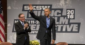 U.S. President Barack Obama, right, waves to the audience after speaking with Evan Smith, chief executive officer and editor-in-chief of The Texas Tribune, during the South By Southwest (SXSW) Interactive Festival in Austin, Texas