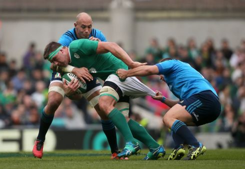 Ireland's CJ Stander is pulled back by Italy's Andrea Lovotti.  Photograph:  Niall Carson/PA Wire.