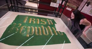 Examining the Irish  Republic flag which flew over the GPO during the 1916 Rising is the Proclaiming a Republic exhibition curator, Brenda Malone. Photograph: Dave Meehan/The Irish Times