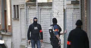 Police at the scene in Brussels where shots were fired during a police search of a house in the suburb of Forest. Photograph: Yves Herman/Reuters