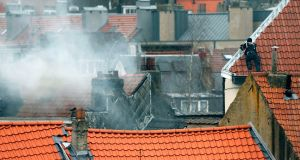 A masked Belgian policeman secures the area from a rooftop above the scene where shots were fired during a police search of a house in the suburb of Forest near Brussels, Belgium. Photograph: Francois Lenoir /Reuters