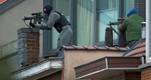 Masked Belgian police secure the area from a rooftop near the scene where shots were fired during a police search of a house in the suburb of Forest near Brussels, Belgium. Photograph: Yves Herman /Reuters