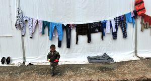 A migrant child stands at a makeshift camp at the Greek-Macedonian border, near the Greek village of Idomeni. Photograph: Sakis Mitrolidis/AFP/Getty Images