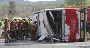 Firemen work at the site of a coach crash that has left at least 14 students dead  in Freginals, in the province of Tarragona, northeastern Spain, on Sunday. Photograph: EPA