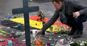 Tributes paid in Brussels: A man places flowers on a street memorial following Tuesday's bomb attacks in Brussels, Belgium, March 23rd, 2016. Photograph: Francois Lenoir/Reuters