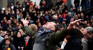 A man reacts as people gather to observe a minute of silence in memory of the victims of the Brussels airport and metro bombings, on the Place de la Bourse in central Brussels. Photograph: AFP