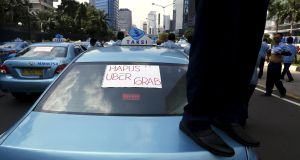 A Jakarta taxi driver stands on his car during a protest against transportation apps with a sign reading 'Remove!! Uber, Grab'. Four men torched a car from the lift hailing company Uber in the Kenyan capital Nairobi on Wednesday, police said. Photograph: Beawiharta/Reuters.