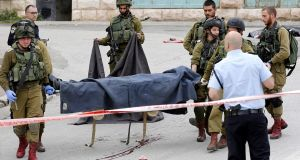 Israeli soldiers carry a body of a dead Palestinian from the scene of a shooting in Tal Rumaida in the West Bank city of Hebron on Thursday. Photograph: Abed al Hashlamoun/EPA