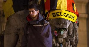 Bear witness: A man cloaked in a Belgian flag looks on as hundreds of people at a makeshift memorial gather before Brussels Stock Exchange on Place de la Bourse. Photograph: Getty Images