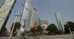 A cyclist crosses a road between skyscrapers in the southern Chinese city of Shenzhen. Photograph:  PETER PARKS/AFP/Getty Images)