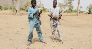 Boys hold bows and arrows in Kerawa, Cameroon. Kerawa is on the border with Nigeria and is subject to frequent Boko Haram attacks. Photograph: Joe Penney/Reuters