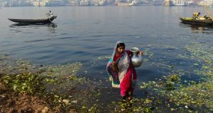 A Bangladeshi woman collecting water from the polluted Buriganga in Dhaka. Some 20 million poor Bangladeshis are still drinking water contaminated with arsenic. Photograph: AFP Photo
