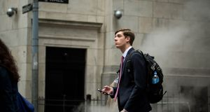 A pedestrian on Wall Street. For  bankers, scuttled deals cost money.  Photograph: Bloomberg