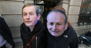 Protesters wearing masks of Enda Kenny  and Micheál Martin.  The difficulties of bringing the two parties together are underrated. Photograph: Nick Bradshaw