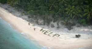 "Two men waiving life jackets next to a large ""Help"" sign made of palm leaves as a US Navy P-8A maritime surveillance aircraft spotted them on the deserted island of Fanadik in Micronesia. Photograph: John Knight/AFP/Getty Images"