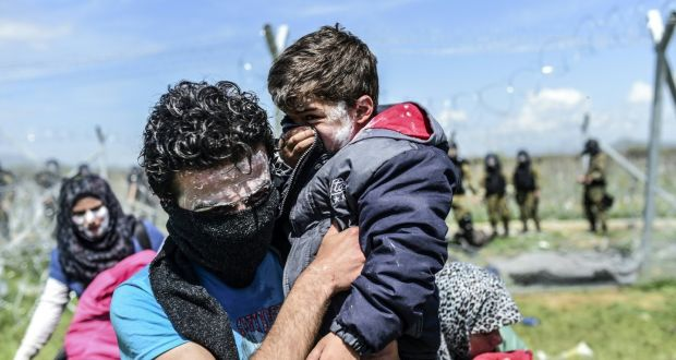 A family with toothpaste smeared over their faces as a protection against tear gas moves to safety as refugees and migrants clash with Macedonian police during a protest near their makeshift camp in the northern Greek border village of Idomeni. Photograph:  Bulent Kilic/AFP/Getty Images