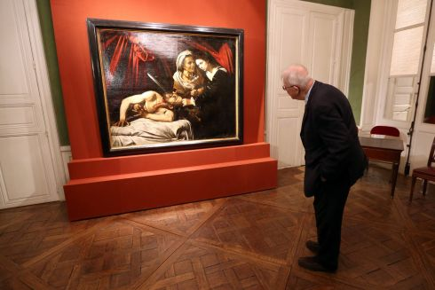 HIDDEN MILLIONS: A visitor looks at a painting entitled Judith Beheading Holofernes during its presentation in Paris, France. Found in a Toulouse attic, it may have been painted by Italian master Caravaggio (1571-1610). Photograph: Charles Platiau/Reuters