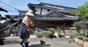 A woman cleans up in front of her collapsed house in the town of Mashiki, Kumamoto prefecture on April 15, 2016.