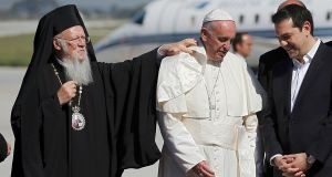 Greek Orthodox Ecumenical Patriarch Bartolomew I adjusts the collar of Pope Francis as he stands with Greek prime minister Alexis Trispras (R) on arrival on the Greek Island of Lesbos. Photograph: Reuters