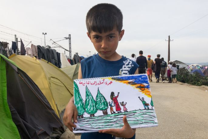 """An unnamed Syrian refugee boy shows his painting book where he has painted scenes from the war at Syria and his travel to Idomeni refugee camp on the Greek-Macedonia borders. The writing says """"hope in Germany"""" and the painting shows the father leaving and his family waving goodbye.  All photographs: Kostas Pikoulas"""