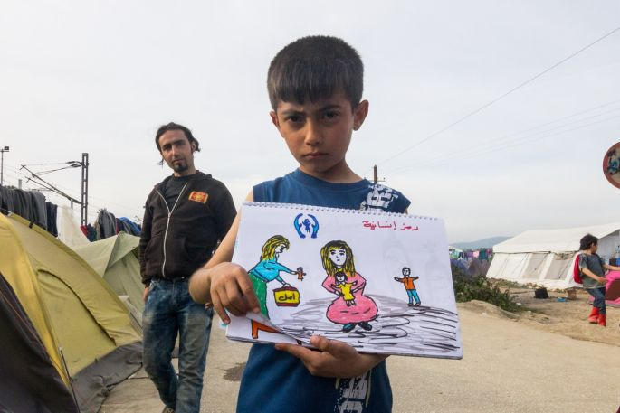"""The writing says """"humanity isn't any good"""", as the painting shows a woman representing UN, giving a doll to a mother, which isn't much use under these conditions."""