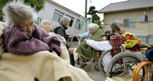 Evacuees from a nursing home  seek safety outside. Photograph: Reuters/Kyodo