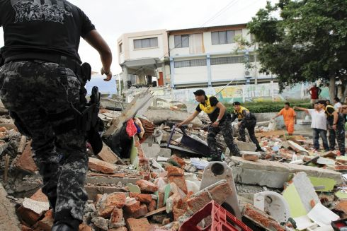 ECUADOR REELING: Red Cross members, military and police officers work at a collapsed area at the Tarqui neighborhood in Manta. Photograph: Guillermo Granja