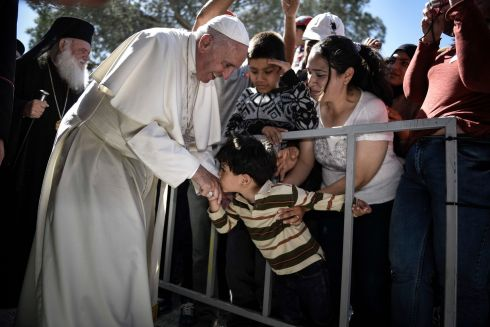 POPE FRANCIS: A child kisses the pontiff's hand during a visit at the Moria refugee camp on the island of Lesbos. Photograph: Andrea Bonetti/Greek Prime Minister's Office via AP