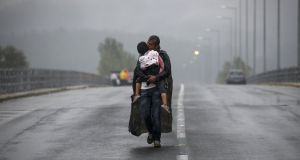 A Syrian refugee kisses his daughter as he walks through a rainstorm towards Greece's border with Macedonia, near Idomeni in September. Photograph: Yannis Behrakis/Reuters