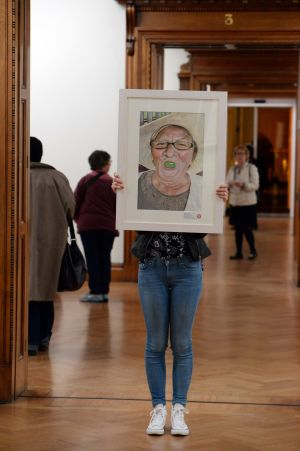 Marta Turalska, from Newcastle West, Limerick, is hidden from view with her winning picture of her grandmother, which took first prize overall in  the Texaco Children's Art Competition. Photograph: Cyril Byrne/The Irish Times