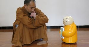 Master Xianfan looks at robot monk Xian'er as he demonstrates the robot's conversation function during a photo opportunity in Longquan Buddhist temple on the outskirts of Beijing recently. Photograph: Kim Kyung-Hoon/Reuters