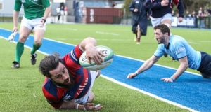 Clontarf's Mick McGrath scores a try against UCD. Photograph: Gary Carr/Inpho