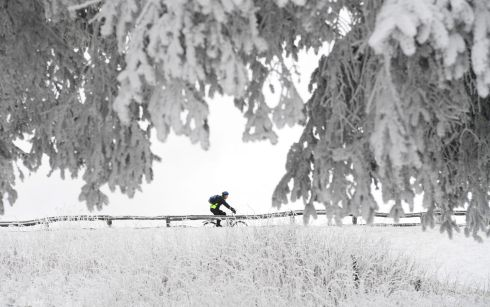 GERMANY: A mountain biker rides over the snow-covered Feldberg mountain in the Taunus mountains near Oberreifenberg, Germany. Photograph: Arne Dedert/EPA