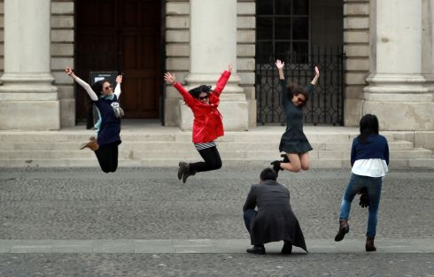 JUMP: Visitors to Trinity College Dublin pose for a photograph in the main square. Photograph: Nick Bradshaw