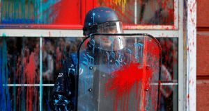 A police officer holds his shield as protestors pelt the facade of the Ministry of Justice with  paint. Photograph: Boris Grdanoski/AP Photo