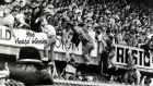 Liverpool fans are pulled to safety on to the upper tier to escape the crush on the terrace below. Photograph: Bob Thomas/Getty Images