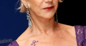 Actor Helen Mirren points to a Prince symbol she is wearing as she arrives at the annual White House Correspondents' Association Dinner in Washington DC, US. Photograph: Jonathan Ernst/Reuters