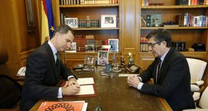 Spain's King Felipe signs a decree to dissolve parliament and call new elections during a meeting with parliamentary speaker Patxi Lopez at the Zarzuela Palace in Madrid. Photograph: Courtesy of Casa de S.M. el Rey/Handout via Reuters